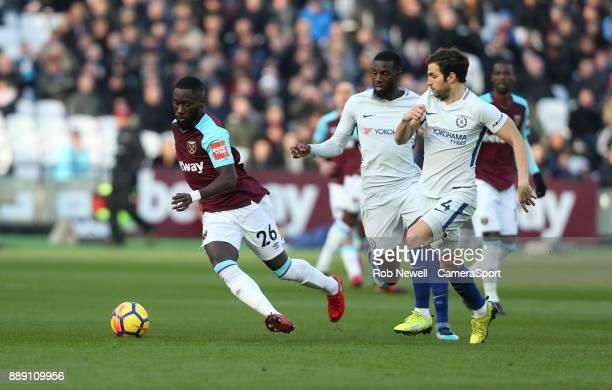 West Ham United's Arthur Masuaku dribbles away from Chelsea's Cesc Fabregas and Tiemoue Bakayoko during the Premier League match between West Ham...