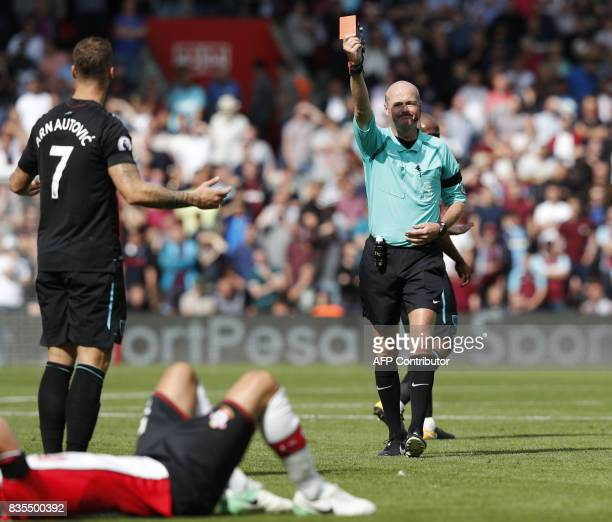 West Ham United's Austrian midfielder Marko Arnautovic gestures as referee Lee Mason gives him a red card as Southampton's Gabonese midfielder Mario...
