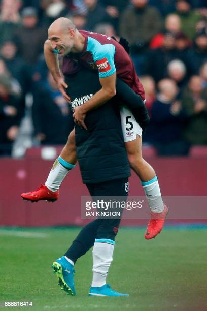 West Ham United's Austrian midfielder Marko Arnautovic picks up West Ham United's Argentinian defender Pablo Zabaleta as they celebrate on the pitch...