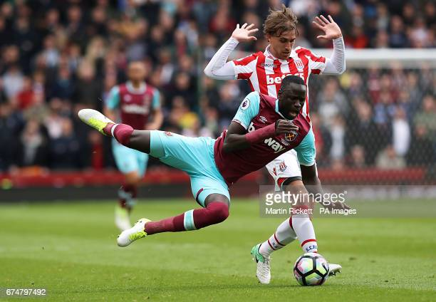 West Ham United's Cheikhou Kouyate and Stoke City's Marc Muniesa battle for the ball during the Premier League match at the bet365 Stadium Stoke
