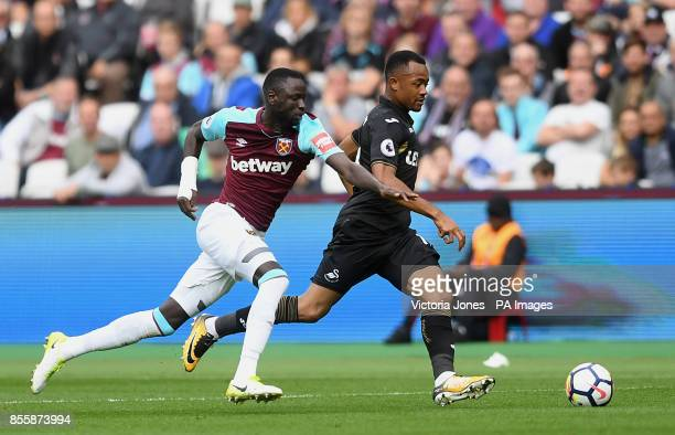 West Ham United's Cheikhou Kouyate and Swansea City's Jordan Ayew battle for the ball during the Premier League match at London Stadium