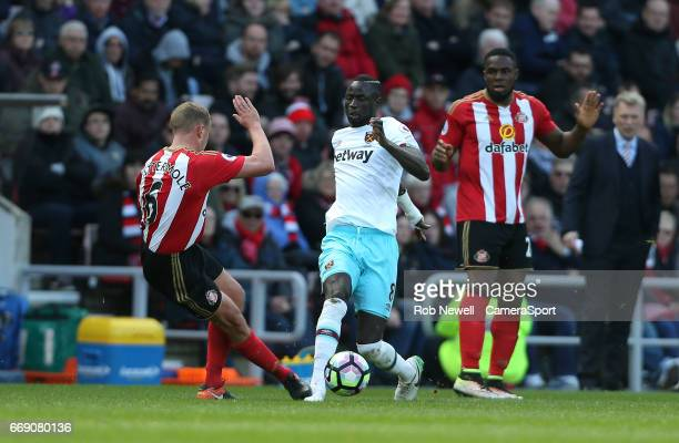 West Ham United's Cheikhou Kouyate is challenged by Sunderland's Lee Cattermole during the Premier League match between Sunderland and West Ham...