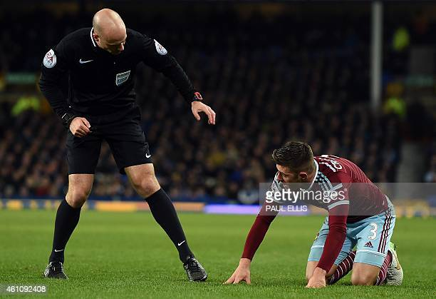 West Ham United's English defender Aaron Cresswell is spoken to by referee Anthony Taylor during the English FA Cup Third Round football match...