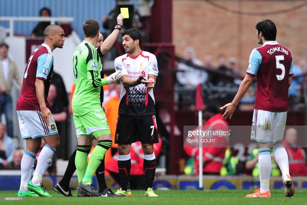 West Ham United's English defender James Tomkins (R) is given a yellow card for handball in the area to concede a penalty by referee Anthony Taylor (3L) as Liverpool's Uruguayan striker Luis Suarez (2R) gestures during the English Premier League football match between West Ham United and Liverpool at Upton Park in London on April 6, 2014. AFP PHOTO / CARL COURT USE. No use with unauthorized audio, video, data, fixture lists, club/league logos or live services. Online in-match use limited to 45 images, no video emulation. No use in betting, games or single club/league/player publications.
