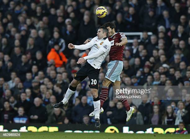 West Ham United's English defender James Tomkins vies with Manchester United's Dutch striker Robin van Persie during the English Premier League...