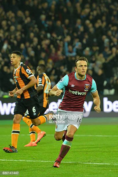 West Ham United's English midfielder Mark Noble celebrates after scoring the opening goal from the penalty spot during the English Premier League...
