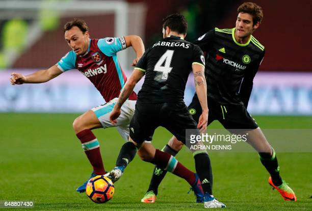 West Ham United's English midfielder Mark Noble vies with Chelsea's Spanish midfielder Cesc Fabregas during the English Premier League football match...