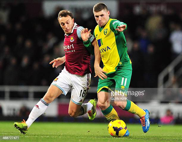 West Ham United's English midfielder Mark Noble vies with Norwich City's English striker Gary Hooper during the English Premier League football match...