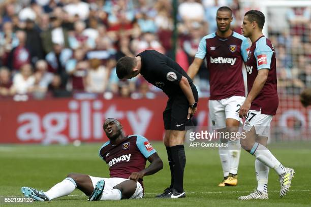 West Ham United's English midfielder Michail Antonio clutches his thigh after being knocked during the English Premier League football match between...