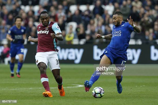 West Ham United's English midfielder Michail Antonio vies with Leicester City's English defender Danny Simpson during the English Premier League...