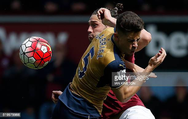 West Ham United's English striker Andy Carroll clashes inthe air with Arsenal's Brazilian defender Gabriel during the English Premier League football...