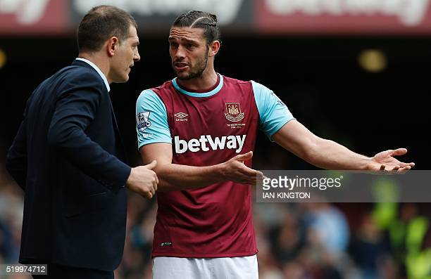 West Ham United's English striker Andy Carroll gestures as he speaks with West Ham United's Croatian manager Slaven Bilic during the English Premier...
