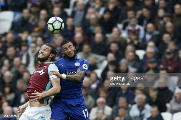 West Ham United's English striker Andy Carroll jumps for a header with Leicester City's English defender Danny Simpson during the English Premier...