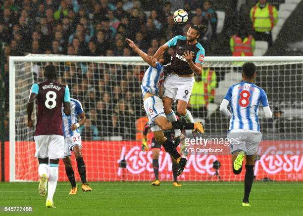 West Ham United's English striker Andy Carroll jumps for a header with Huddersfield Town's German defender Christopher Schindler during the English...