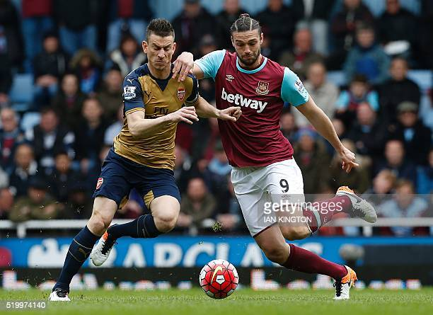 West Ham United's English striker Andy Carroll vies with Arsenal's French defender Laurent Koscielny during the English Premier League football match...