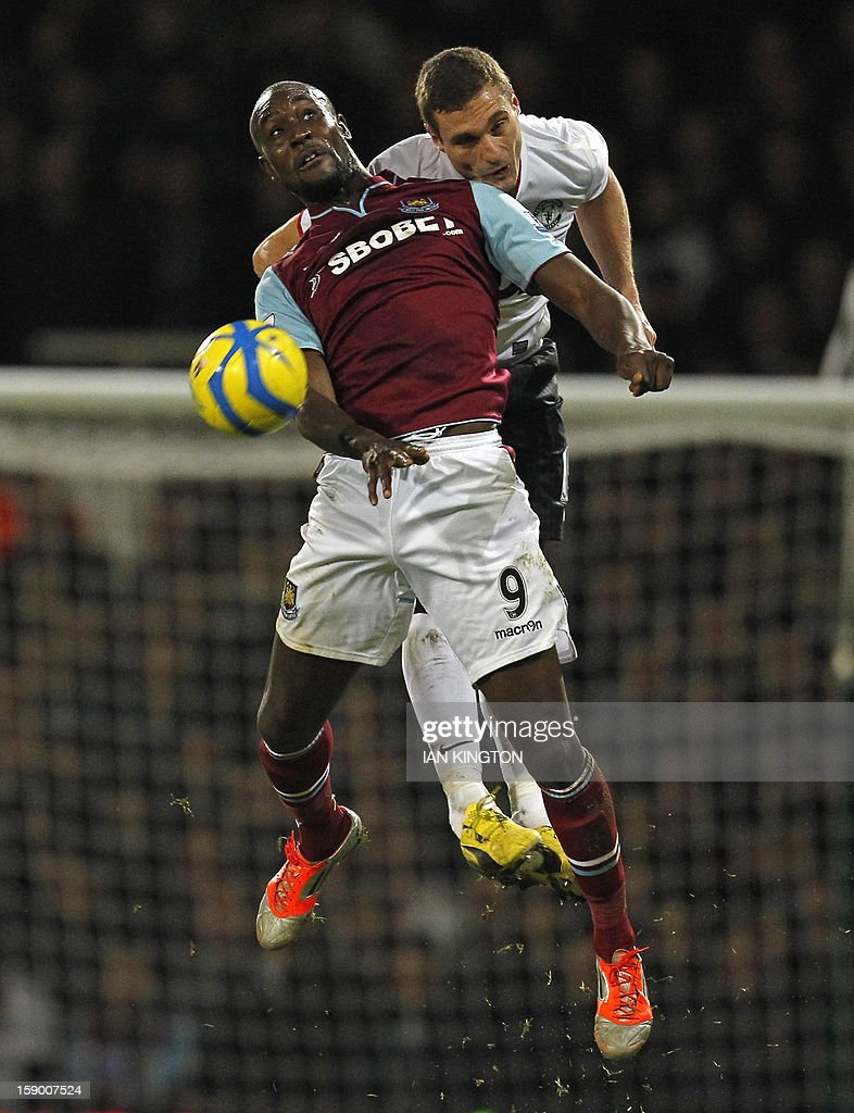 """West Ham United's English striker Carlton Cole (L) vies with Manchester United's Serbian defender Nemanja Vidic (R) during the English FA Cup third round football match between West Ham United and Manchester United at the Boleyn Ground, Upton Park, in East London on January 5, 2013. The game finished 2-2. USE. No use with unauthorized audio, video, data, fixture lists, club/league logos or """"live"""" services. Online in-match use limited to 45 images, no video emulation. No use in betting, games or single club/league/player publications."""