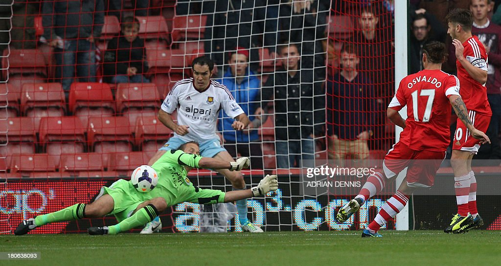 West Ham United's Finnish goalkeeper Jussi Jaaskelainen (L) dives across his goal to save a shot from Southampton's Argentinian-born Italian striker Dani Osvaldo (2R) during English Premier League football match between Southampton and West Ham United at St Mary's Stadium in Southampton, southern England, on September 15, 2013. AFP PHOTO / ADRIAN DENNIS USE. No use with unauthorized audio, video, data, fixture lists, club/league logos or 'live' services. Online in-match use limited to 45 images, no video emulation. No use in betting, games or single club/league/player publications.