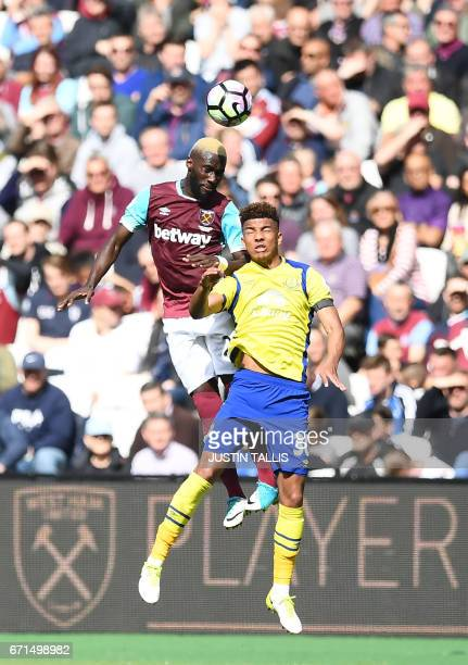 West Ham United's French defender Arthur Masuaku jumps for a header with Everton's English defender Mason Holgate during the English Premier League...