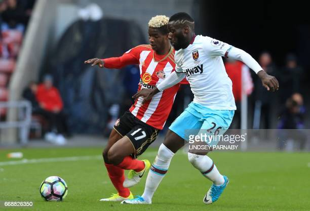 West Ham United's French defender Arthur Masuaku vies for the ball with Sunderland's Gabonese midfielder Didier N'Dong during the English Premier...