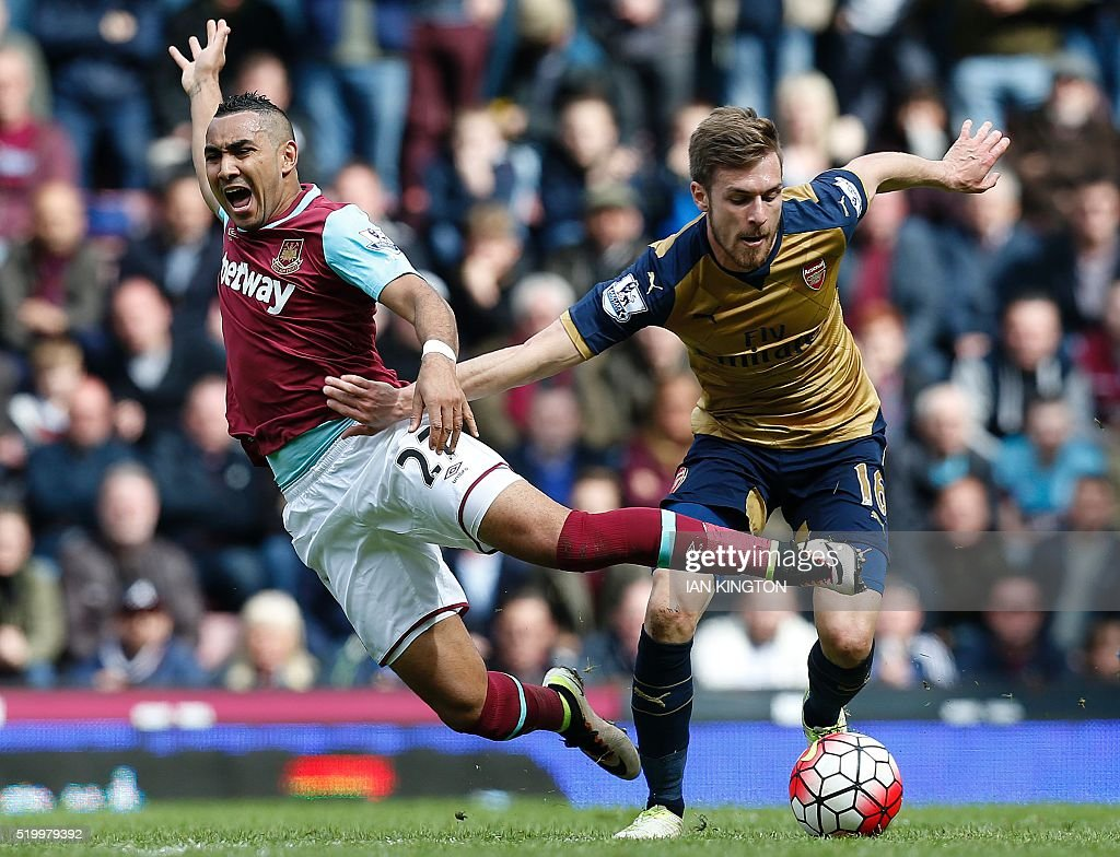 West Ham United's French midfielder Dimitri Payet (L) vies with Arsenal's Welsh midfielder Aaron Ramsey during the English Premier League football match between West Ham United and Arsenal at The Boleyn Ground in Upton Park, in east London on April 9, 2016. / AFP / Ian Kington / RESTRICTED TO EDITORIAL USE. No use with unauthorized audio, video, data, fixture lists, club/league logos or 'live' services. Online in-match use limited to 75 images, no video emulation. No use in betting, games or single club/league/player publications. /