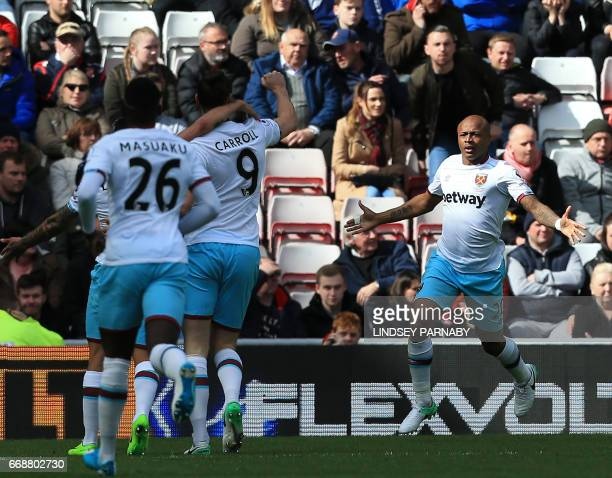 West Ham United's Frenchborn Ghanaian midfielder Andre Ayew celebrates scoring the opening goal with teammates during the English Premier League...