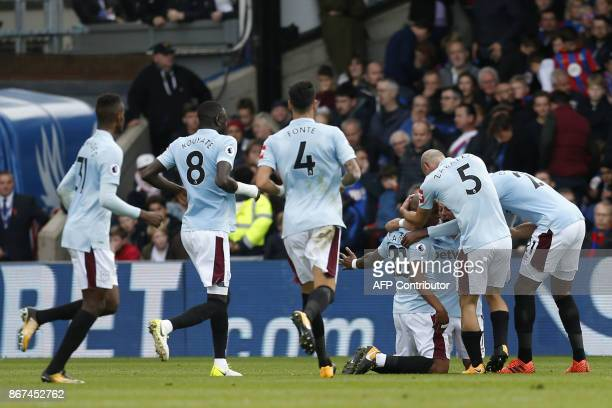 West Ham United's Frenchborn Ghanaian midfielder Andre Ayew celebrates with teammates scoring the team's second goal during the English Premier...