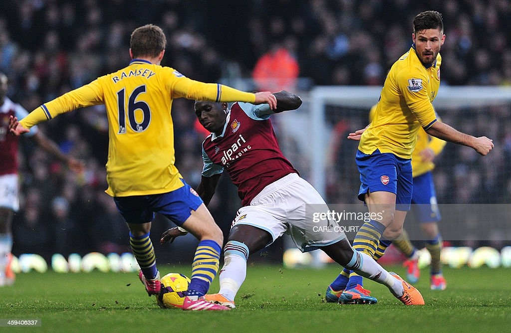 West Ham United's French-born Senegalese midfielder Mohamed Diame (C) vies with Arsenal's Welsh midfielder Aaron Ramsey (L) and Arsenal's French forward Olivier Giroud during the English Premier League football match between West Ham United and Arsenal at the Boleyn Ground, Upton Park, in east London on December 26, 2013. USE. No use with unauthorized audio, video, data, fixture lists, club/league logos or live services. Online in-match use limited to 45 images, no video emulation. No use in betting, games or single club/league/player publications.