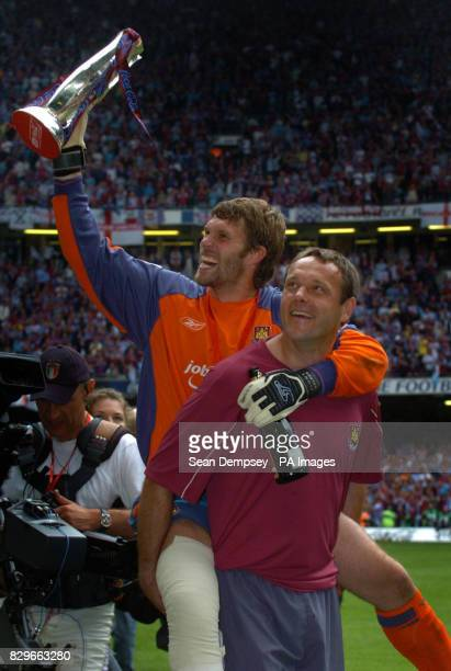 West Ham United's injured keeper Jimmy Walker holds the play off trophy whilst carried around the pitch by goalkeeper coach Ludo Miklosko after they...