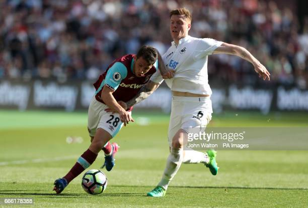 West Ham United's Jonathan Calleri and Swansea City's Alfie Mawson battle for the ball during the Premier League match at the London Stadium