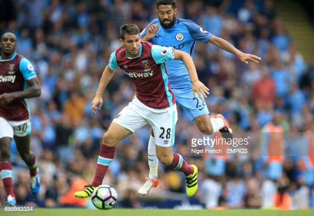 West Ham United's Jonathan Calleri holds off Manchester City's Gael Clichy