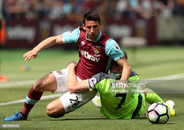 West Ham United's Jonathan Calleri trips over Liverpool's James Milner during the Premier League match at London Stadium