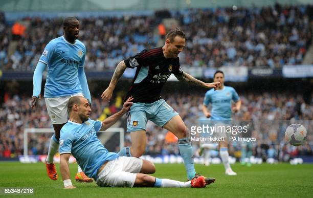 West Ham United's Matthew Taylor battles for the ball with Manchester City's Pablo Zabaleta during the Barclays Premier League match at the Etihad...