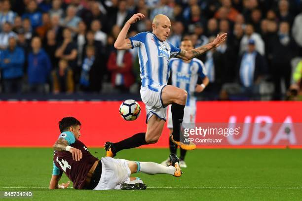 West Ham United's Portuguese defender Jose Fonte tackles Huddersfield Town's Australian midfielder Aaron Mooy during the English Premier League...