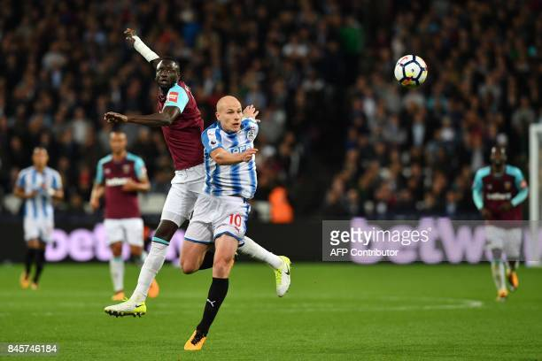 West Ham United's Senegalese midfielder Cheikhou Kouyate and Huddersfield Town's Australian midfielder Aaron Mooy vie for the ball during the English...