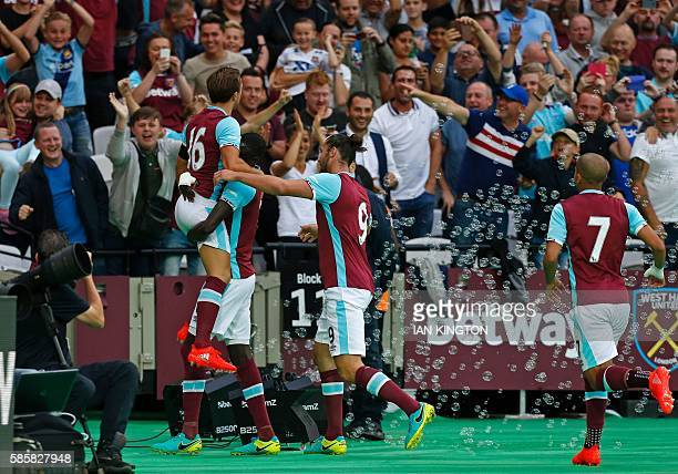 West Ham United's Senegalese midfielder Cheikhou Kouyate and West Ham United's English midfielder Mark Noble celebrate with teammates after taking...