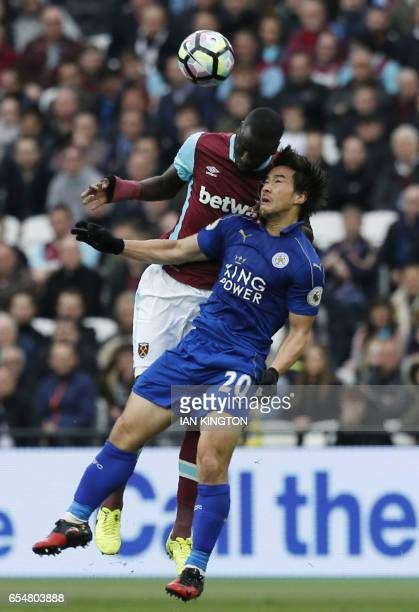West Ham United's Senegalese midfielder Cheikhou Kouyate jumps for a header with Leicester City's Japanese striker Shinji Okazaki during the English...