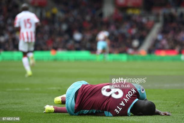 West Ham United's Senegalese midfielder Cheikhou Kouyate lies injured during the English Premier League football match between Stoke City and West...