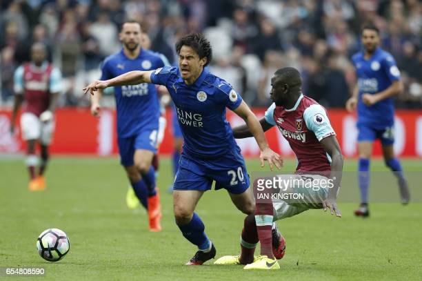 West Ham United's Senegalese midfielder Cheikhou Kouyate tackles Leicester City's Japanese striker Shinji Okazaki during the English Premier League...