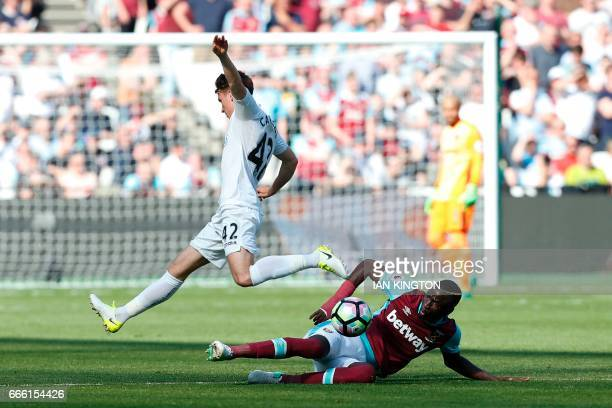 West Ham United's Senegalese midfielder Cheikhou Kouyate tackles Swansea City's English midfielder Tom Carroll during the English Premier League...