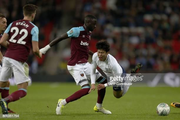 West Ham United's Senegalese midfielder Cheikhou Kouyate tackles Tottenham Hotspur's South Korean striker Son HeungMin during the English League Cup...