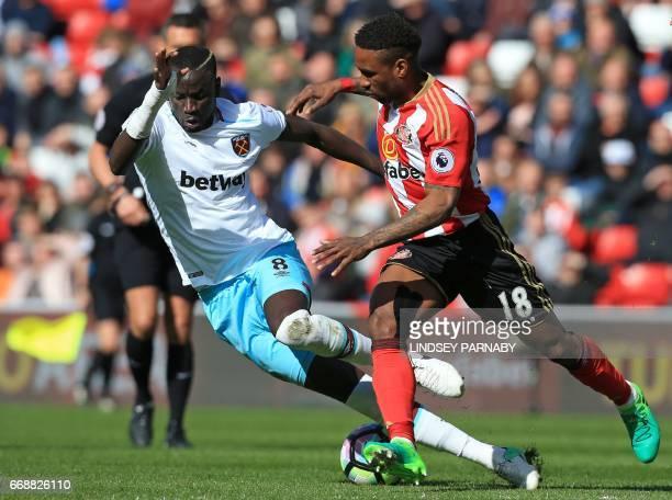West Ham United's Senegalese midfielder Cheikhou Kouyate vies for the ball with Sunderland's English striker Jermain Defoe during the English Premier...
