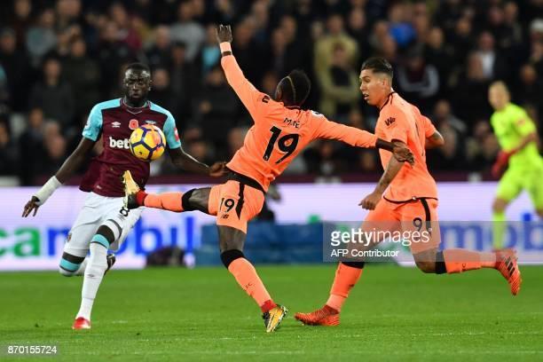 West Ham United's Senegalese midfielder Cheikhou Kouyate vies with Liverpool's Senegalese midfielder Sadio Mane during the English Premier League...