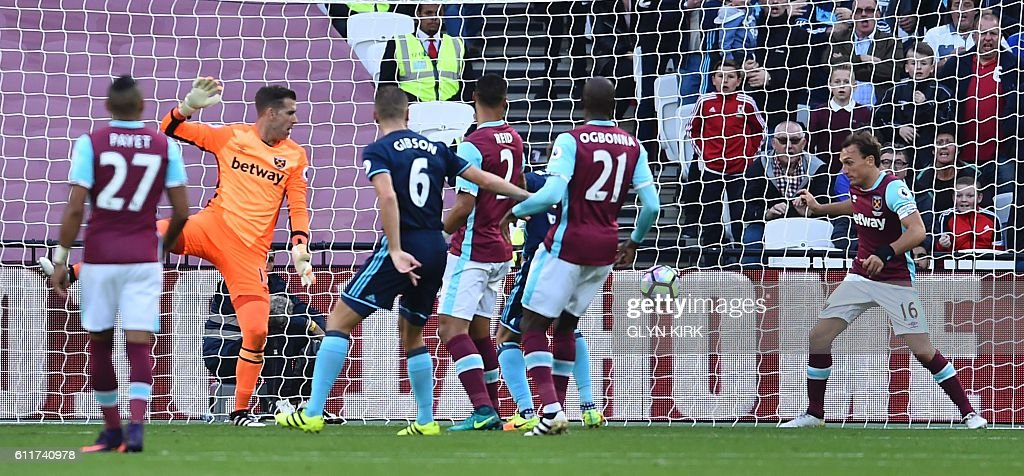 West Ham United's Spanish goalkeeper Adrian (2L) looks back to see the ball going in from a header from Middlesbrough's Uruguayan striker Christian Stuani for the opening goal as West Ham United's English midfielder Mark Noble (R) tries to clear off the line during the English Premier League football match between West Ham United and Middlesbrough at The London Stadium, in east London on October 1, 2016. / AFP / GLYN KIRK / RESTRICTED TO EDITORIAL USE. No use with unauthorized audio, video, data, fixture lists, club/league logos or 'live' services. Online in-match use limited to 75 images, no video emulation. No use in betting, games or single club/league/player publications. /