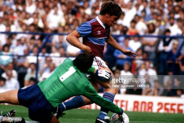 West Ham United's Tony Cottee rounds Tottenham Hotspur goalkeeper Ray Clemence