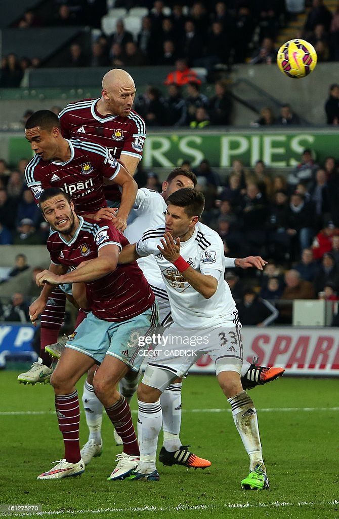 West Ham United's Welsh defender <a gi-track='captionPersonalityLinkClicked' href=/galleries/search?phrase=James+Collins+-+Welsh+Soccer+Player&family=editorial&specificpeople=15167252 ng-click='$event.stopPropagation()'>James Collins</a> (top C) heads toward goal but fails to score during the English Premier League football match between Swansea City and West Ham United at The Liberty Stadium in Swansea, south Wales on January 10, 2015. USE. No use with unauthorized audio, video, data, fixture lists, club/league logos or live services. Online in-match use limited to 45 images, no video emulation. No use in betting, games or single club/league/player publications.