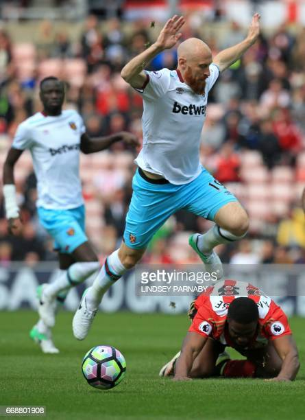 West Ham United's Welsh defender James Collins jumps over Sunderland's Nigerian striker Victor Anichebe during the English Premier League football...