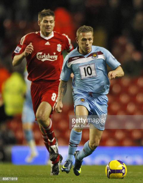 West Ham United's Welsh forward Craig Bellamy plays the ball away from Liverpool's English midfielder Steven Gerrard during their English Premier...
