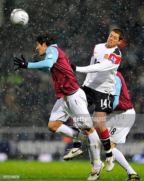 West Ham's English defender James Tomkins vies with Manchester United's Mexican striker Javier Hernandez during their quarter final League Cup...
