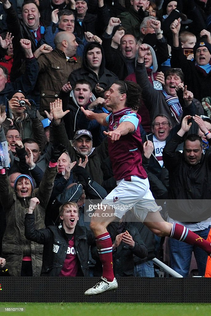 """West Ham's English striker Andy Carroll celebrates after scoring the opening goal of the English Premier League football match between West Ham United and West Bromwich Albion at Upton Park in east London on March 30, 2013. USE. No use with unauthorized audio, video, data, fixture lists, club/league logos or """"live"""" services. Online in-match use limited to 45 images, no video emulation. No use in betting, games or single club/league/player publications. """""""