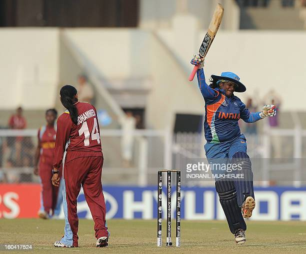 West Indian cricketer Anisa Mohammed looks on as Indian cricketer Thirush Kamini jumps in the air as she celebrates her century during the inaugural...